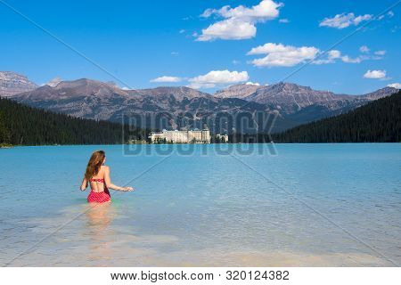 A Woman Gonna Swimming In The Cold Clear Water Of Lake Louise And Looks At The Fairmont Chateau Hote