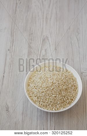 Organic Arborio Rice In A White Bowl On A White Wooden Background, Low Angle View. Copy Space.