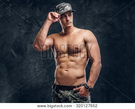 Handsome Shirtless Man In Cap Is Posing For Photographer At Dark Photo Studio.