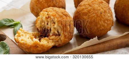 Homemade Fried Arancini With Basil On A Rustic Wooden Board, Side View. Italian Rice Balls. Closeup.
