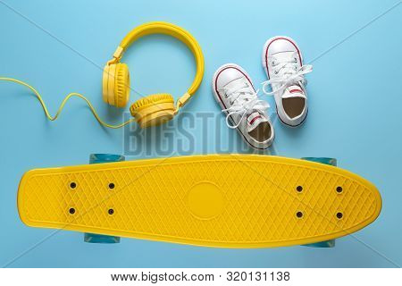 Yellow Headphones, White Sneakers And Skateboard Or Pennyboard On Blue Background. Music Concept.