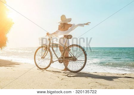 Happiness woman traveler with her bicycle rides on sea coastline and looking on beautifull seascape view in sunny summer day on beach. Freedom, Travell, Journej,  concept.