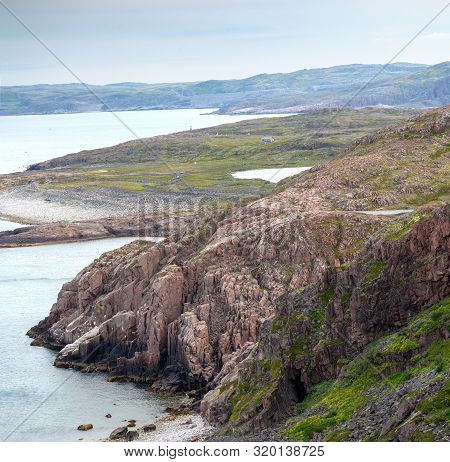 Top View Of The Rocky Steep Coast Of The Barents Sea Beyond The Arctic Circle In Summer In Inclement