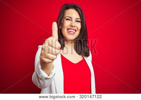 Young beautiful business woman wearing elegant jacket over red isolated background doing happy thumbs up gesture with hand. Approving expression looking at the camera with showing success.