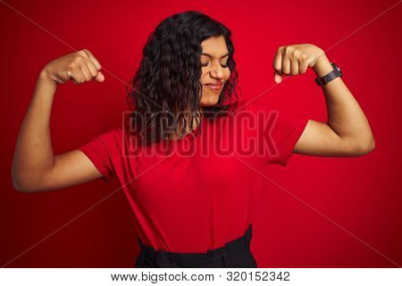 Beautiful transsexual transgender woman wearing t-shirt over isolated red background showing arms muscles smiling proud. Fitness concept.