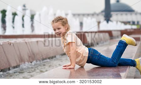 Cute little mischievous girl plays at the fountain. Time of prank. Urban casual outfit. Carefree. Happiness, fun and childhood concept. poster