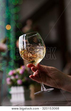 Hand Sommelier Holding Glass Of White Wine. Swirling Wine Glass In Wine Tastings  White Wine Concept