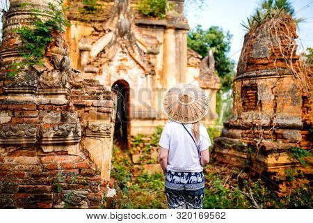 Back view of young woman visiting hundrets of centuries old stupas in Indein near lake Inle in Myanmar