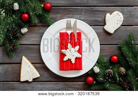 Table Setting With Spruce, Plate, Flatware On Wooden Background Top View