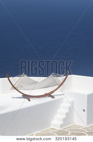 Greece, The Island Of Sikinos. A Hammock Slung On A Terrace Overlooking The Aegean Sea. A Place To U