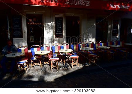 Paris, France. August 12, 2019. Wooden Chairs With The French Flag At Famous Chez Eugene Cafe Restau