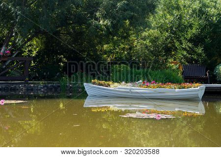 Flowers In A White Boat Floating Freely On The Lake In The Park, A Boat Instead Of A Flower Bed, Lan