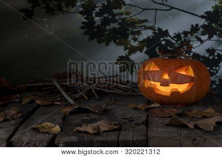 Halloween Pumpkin Glowing In A Mystic  Forest At Night. Jack O Lantern Horror Background. Halloween