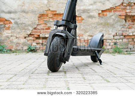 Electric Kick Scooter Or E-scooter Parked On Pavement - E-mobility Or Micro-mobility Trend