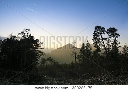 Parched Mountain River. Sunset Over The Dried Riverbed With Trees On The Edge. In The Foreground You