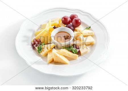 Macro shot of cheese platter with honey, nuts and red grapes on white restaurant plate isolated. Cheese course with mix of yellow gouda, edam and emmental cheeses closeup
