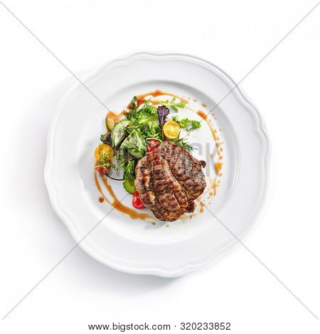 Top view of pork neck steak with mixed salad on white restaurent plate isolated. Restaurant main course with well done meat, veal or beefsteak with tomatoes, fresh parsley, dill and chard topview