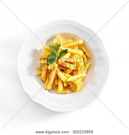 Top view of fries or french fries on white restaurant plate isolated. Sweet potato finger chips, french-fried potatoes, delicious fast food with salt and a leaf of parsley topview
