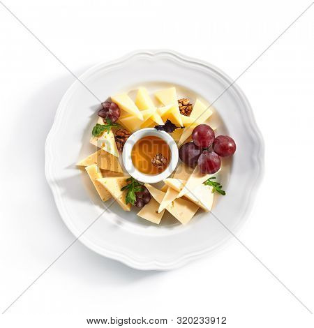 Top view of cheese platter with honey, nuts and red grapes on white restaurant plate isolated. Cheese course with mix of yellow gouda, edam and emmental cheeses topview
