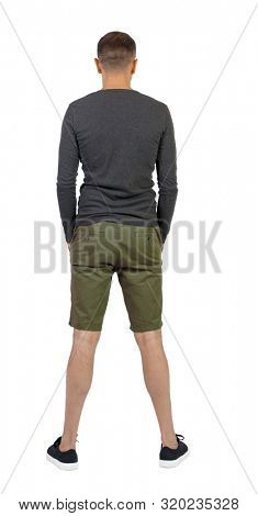 Back view of young manin shorts looking. Rear view people collection. backside view of person. Isolated over white background. A guy in sneakers stands with his hands in his pockets.
