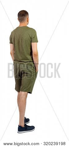 Back view of young manin shorts looking. Rear view people collection. backside view of person. Isolated over white background. The guy in the sneakers looks forward thoughtfully.