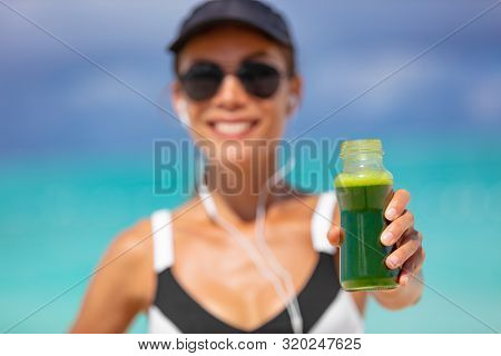 Healthy fit woman showing sports green juice smoothie drink for weight loss detox cleanse. Happy smiling athlete girl holding glass bottle drinking breafkast outside in summer outdoors.