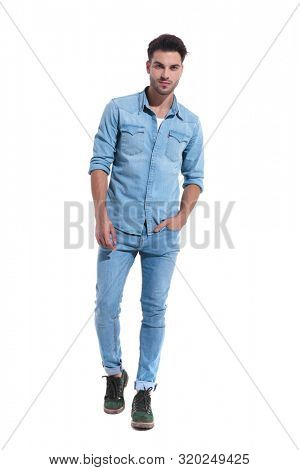 handsome young man walking with a hand in his pocket wearing denim standing isolated on white background; full body, full length