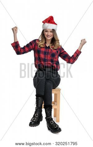 young casual woman in checkered shirt,boots,Christmas hat is sitting on a wooden chair with her hands in the air thrilled on white studio background