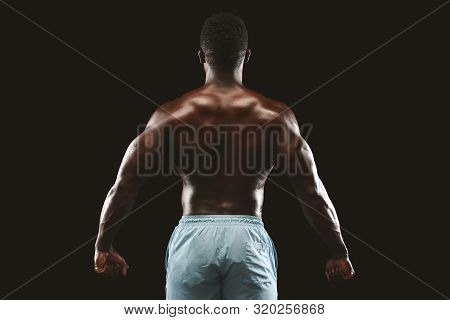 Unrecognizable african bodybuilder showing strong hands and back muscles, athletic trapezius, studio shot on black background poster