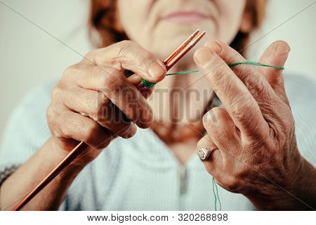 poster of Wool. Woolen clothes. Hands of old woman knitting wool. Adult activity and hand craft. Sweet mature and happy retirement. Calm and quiet lifestyle of old lady at retirement. Knitting