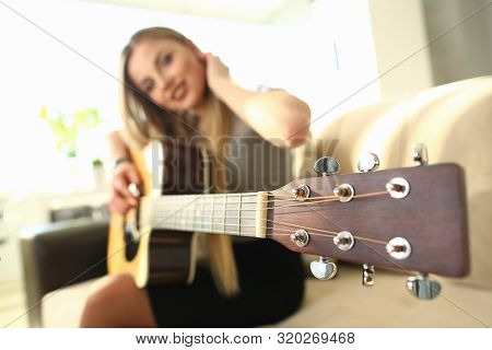Female Bass Guitarist Performing Music At Home. Beautiful Musician Sitting On Comfortable Sofa Holdi