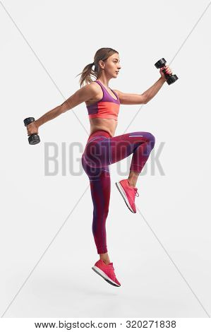 Full Body View Of Muscular Young Female In Sportswear Swinging Arms With Heavy Dumbbells And Leaping