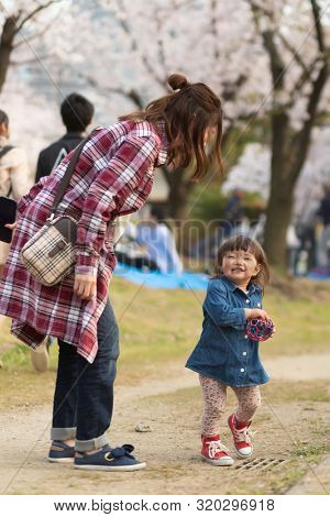 OSAKA, JAPAN, April 7, 2019 : A mother is playing with her daughter in the Kema Sakuranomiya Park during the spring celebration .