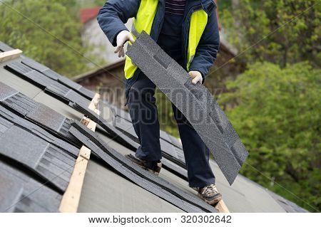 Qualified Collar Worker Or Roofer In Protective Uniform Installing Asphalt Or Bitumen Tile On Top Of
