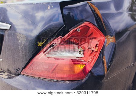 Smashed Headlight. Close-up Of A Smashed Headlight On A Blue Car.