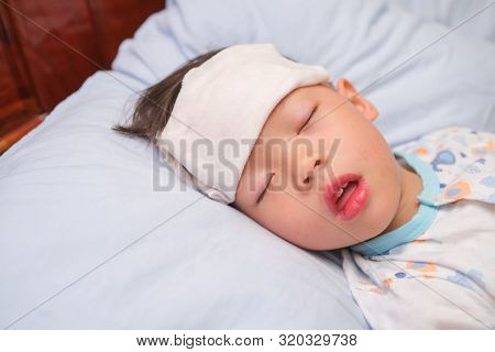 Asian 3 - 4 Years Old Toddler Boy Child Gets High Fever Lying On Bed With Cold Compress, Wet Washclo