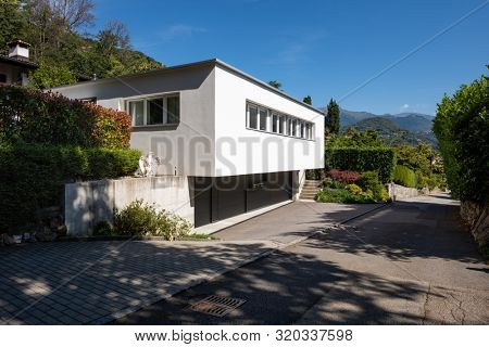 Smal modern white house in Switzerland, it is very romantic situation, long windows.