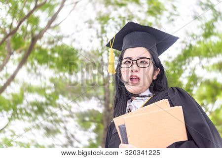 Young Crazy Asian Woman Graduating Holding Diploma With Pride And Funny In An Academic Gown.congratu