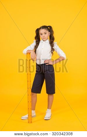Where Student Comes First. Serious Small Student Holding Wooden Ruler On Yellow Background. Little S