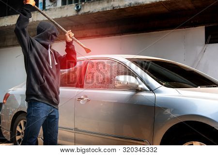 Car Thief Stealing To Break Glass Into A Car .masked Hide Face Man ,robber Dressed In Black Holding