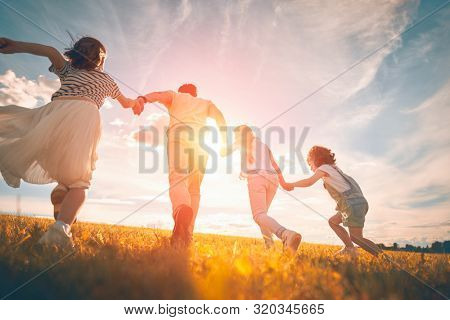 Happy family on autumn walk! Father and daughters walking in the Park and enjoying the beautiful autumn nature.