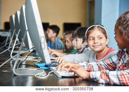 Group of students doing e-learning on the PC in elementary school in computer science course