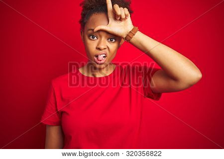 Young beautiful african american woman with afro hair over isolated red background making fun of people with fingers on forehead doing loser gesture mocking and insulting. poster