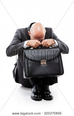 Business problems and failure at work concept - unhappy crying tired or stressed businessman in depression hand holding briefcase sitting down floor white isolated