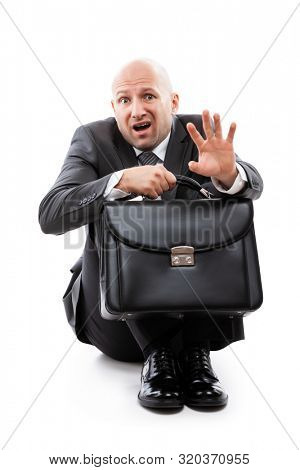 Business problems and failure at work concept - unhappy scared or terrified businessman in depression with fear and stress face expression hand holding briefcase sitting down floor white isolated