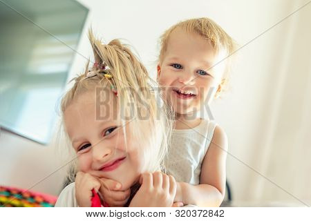 Cute Adorable Blond Caucaian Little Sister Hugging Her Toddler Brother.couple Of Cheerful Sibling Pl
