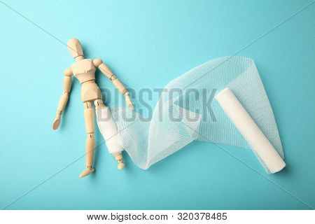 Figure Of Man With Leg Wound And White Gauze Bandage. First Aid, Injury Treatment. Patient In Hospit