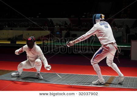 KIEV, UKRAINE - APRIL 14, 2012: Fight between Francesco Martinelli, Italy and Gauthier Grumier, France during World Fencing Championship on April 14, 2012 in Kiev, Ukraine