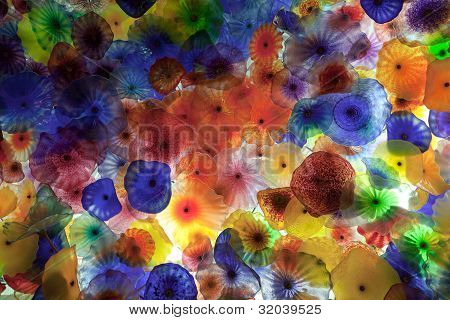 Blown colorful glass flowers backlit by fluorescent light.