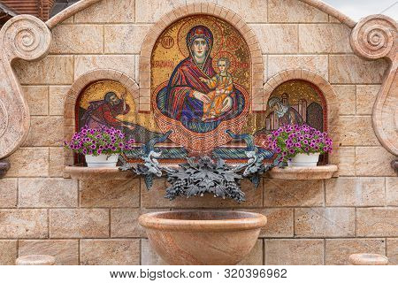 Minsk, Belarus. - May, 2019. Waterworks With Flowers And Mosaical Image Of Mary Virgin With Jesus Ch
